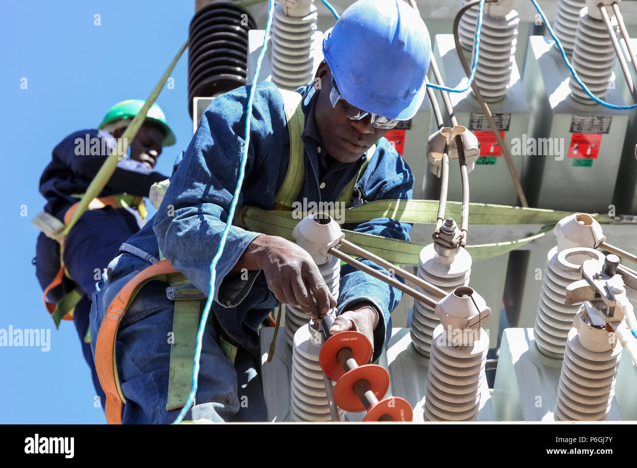 Johannesburg, South Africa, 04/11/2012, Electricians working on high voltage power lines. Highly skilled workmen servicing the electricity grid Stock Photo