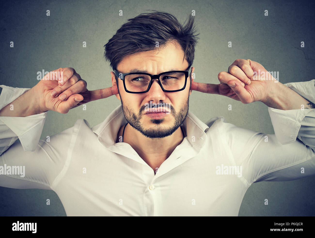 Young displeased man frowning and looking away while closing ears in irritation on gray background - Stock Image