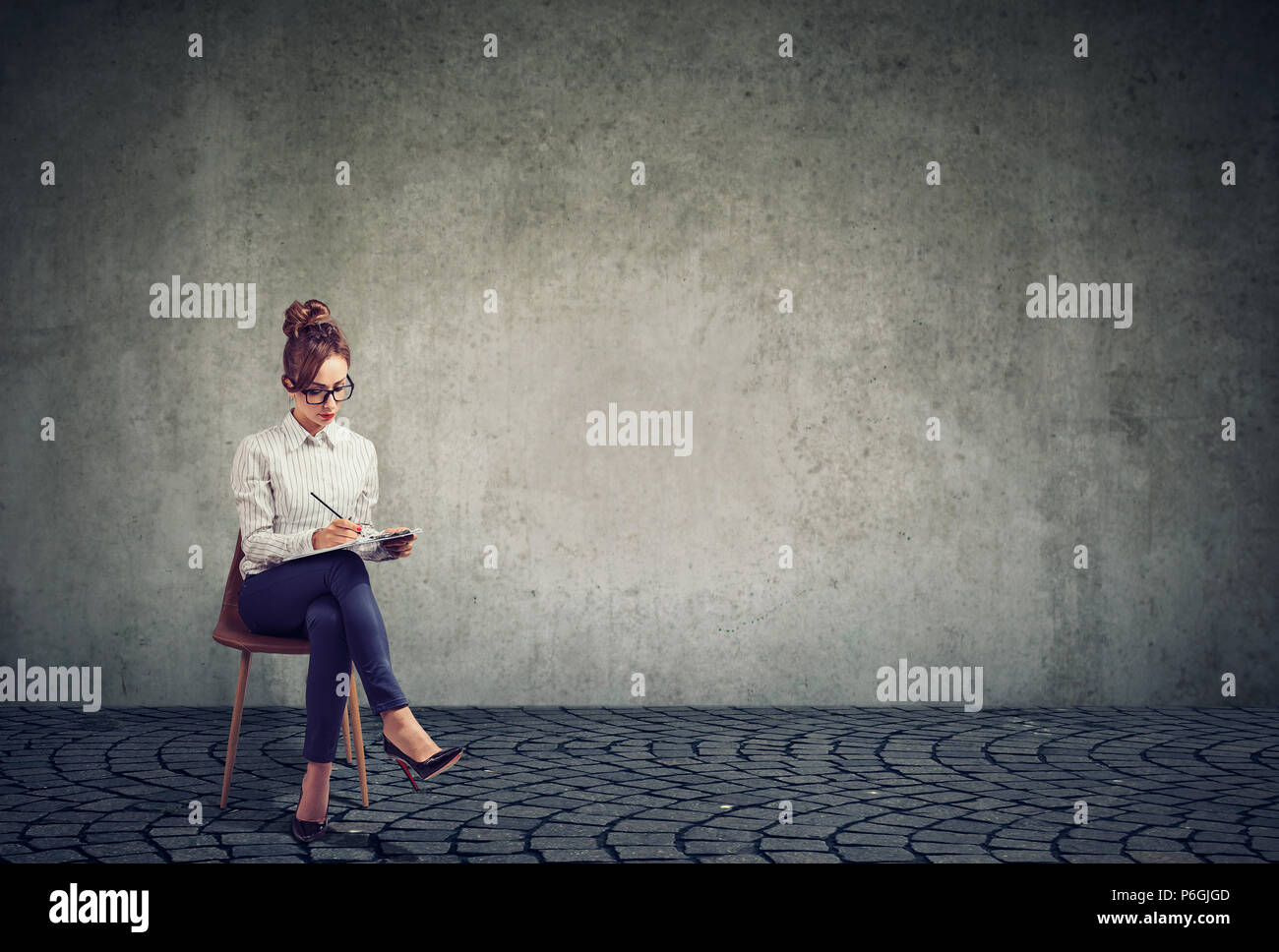39162f241 Stylish woman carrying business and writing on clipboard filling out resume  for job interview while sitting