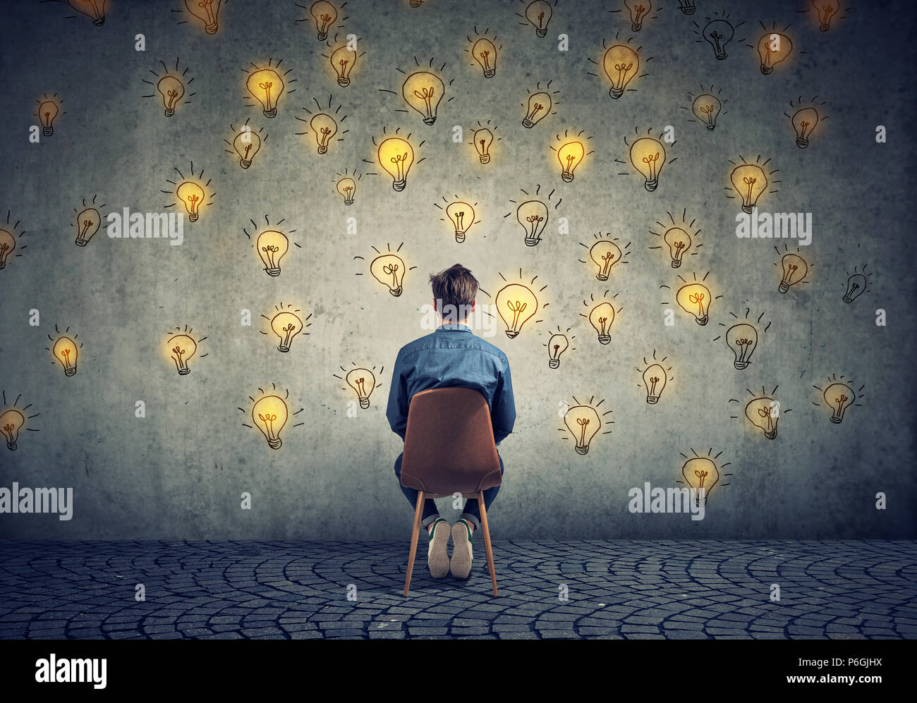 Man sitting on a chair has many bright ideas looking at wall making decisions - Stock Image