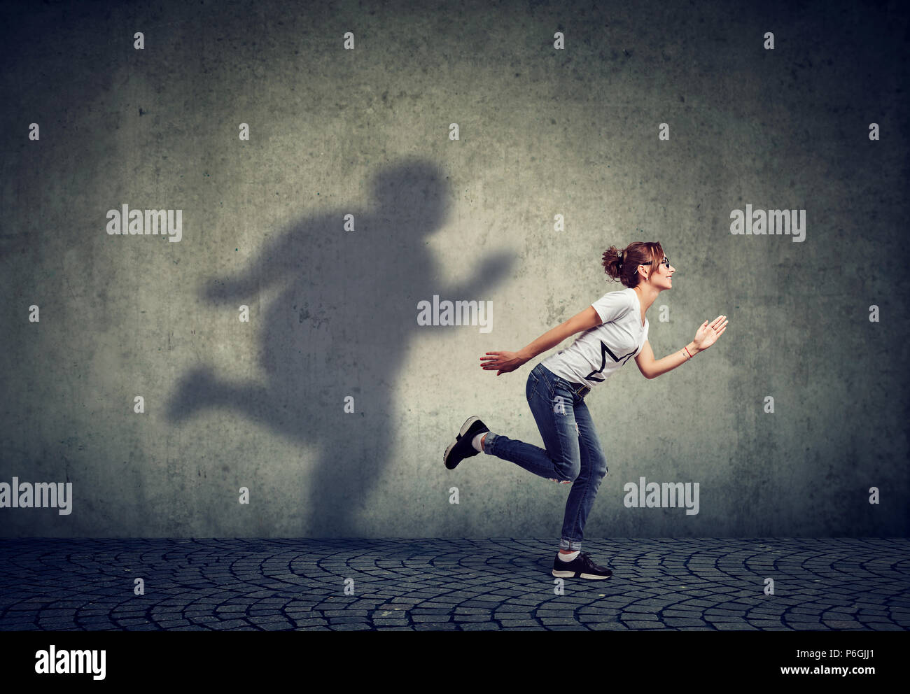 Woman running away from her fat shadow on the wall. Body weight control concept - Stock Image