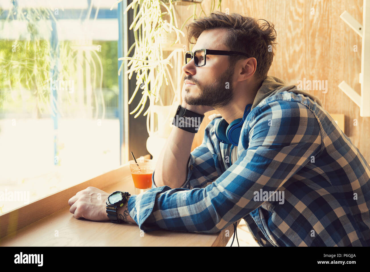 Side view of hipster young man in glasses sitting alone in cafeteria looking away in window in sadness - Stock Image