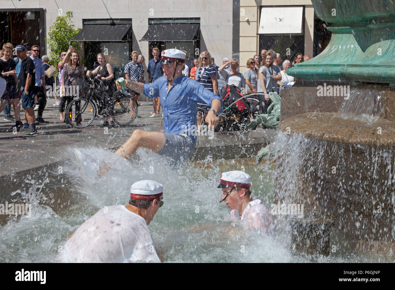 Happy students celebrate their high school graduation and take the plunge into the cold water of the Stork Fountain, Storkespringvandet, in Copenhagen - Stock Image