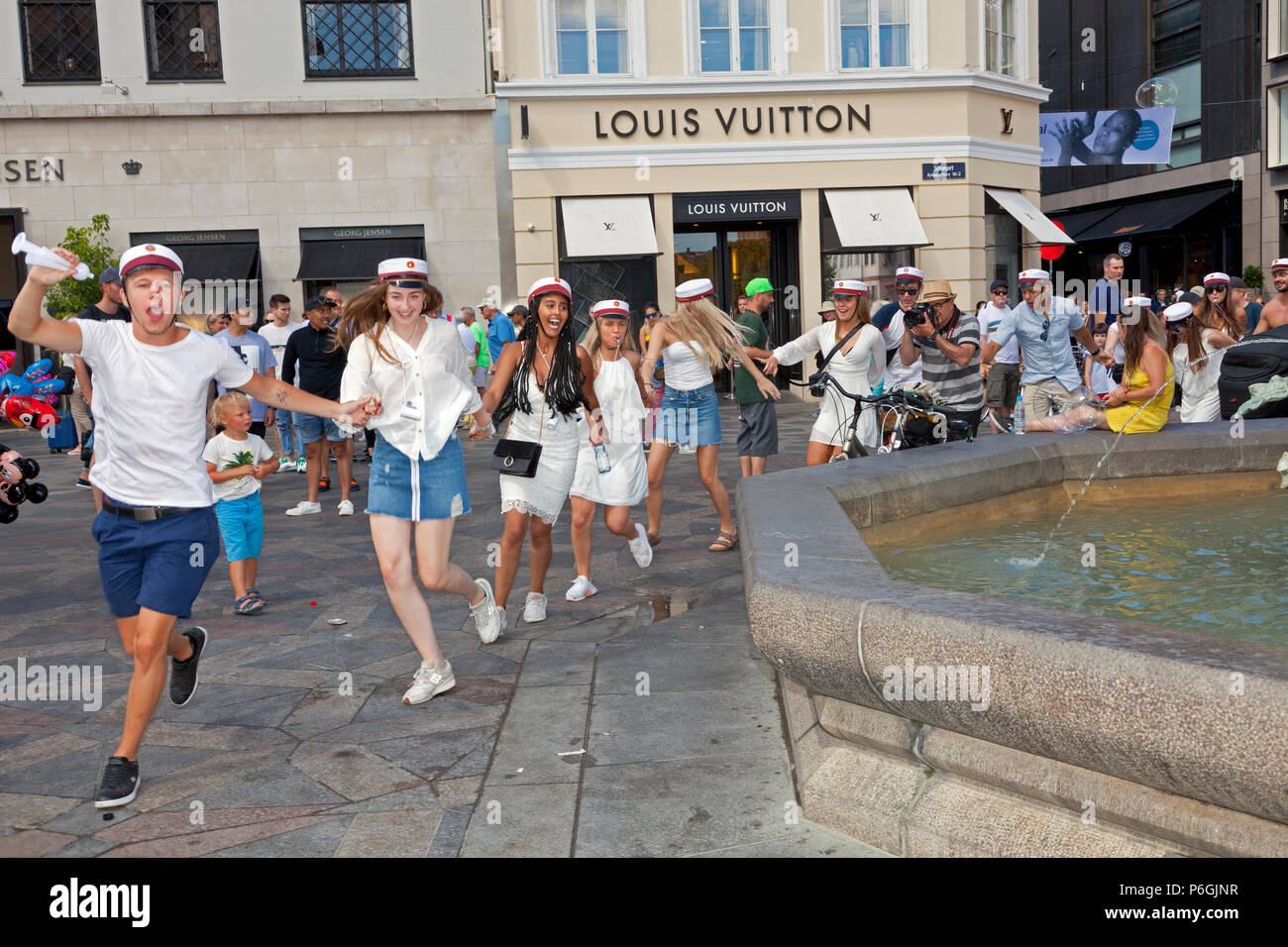 Happy students celebrate their high school graduation and run or dance round the Stork Fountain, Storkespringvandet, in Copenhagen before plunging in. - Stock Image