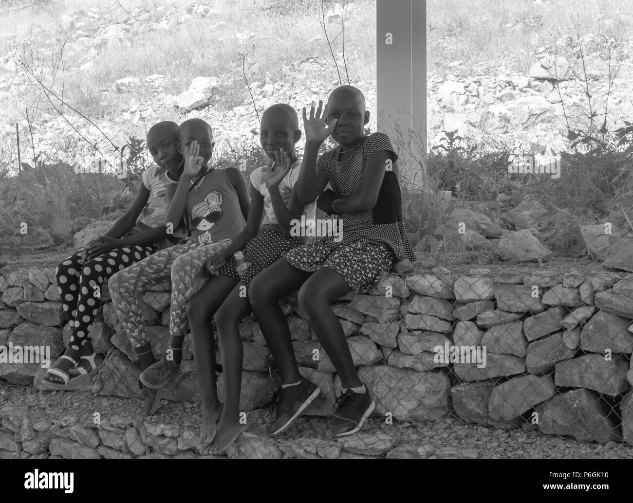 KHOHAXIS, NAMIBIA - MAY 21 2018;  Group of African girls sitting in shade waving happily responding to being photographed in black and white - Stock Image