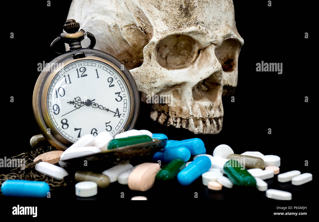 Antique clock on multicolored of drug and capsule behind clock is a skull. is on the black background. Close up. We are against drugs (anti drugs), cu - Stock Image