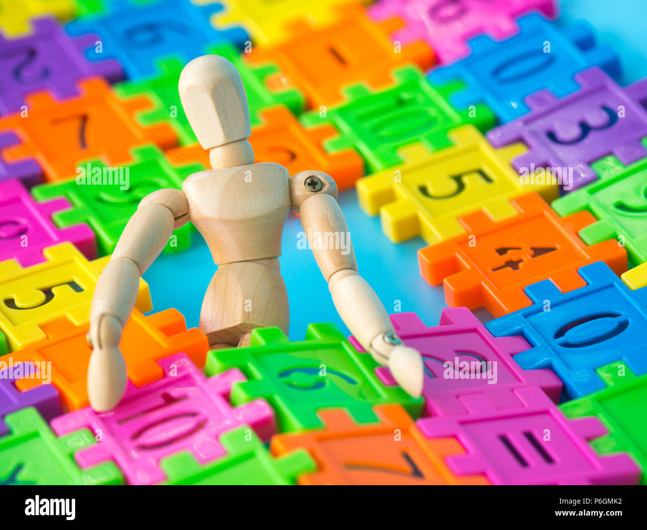 Wooden puppet sit behind colorful plastic number on blue background. Concept of education Stock Photo