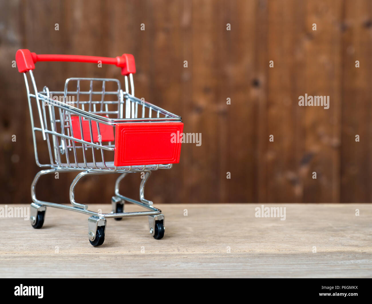 Red shopping cart on wooden table and background is wooden. The concept of shopping and Discount festival - Stock Image