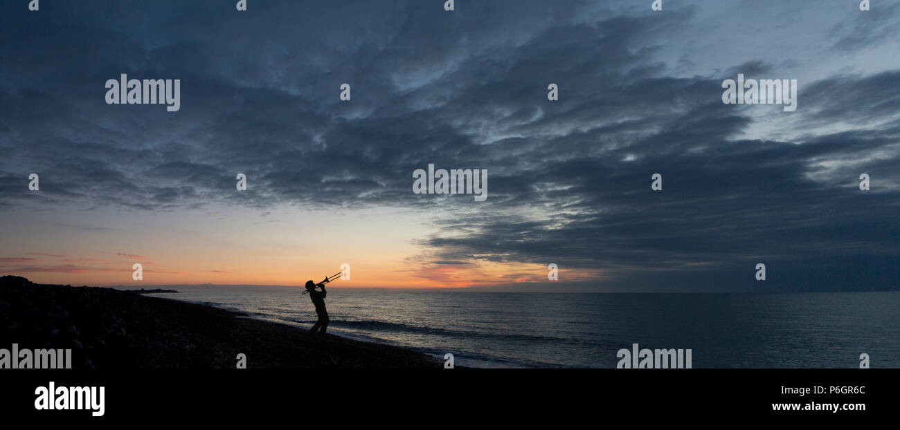 Panorama of a man in silhouette playing a trombone against a sunrise on a beach with early morning clouds - Stock Image
