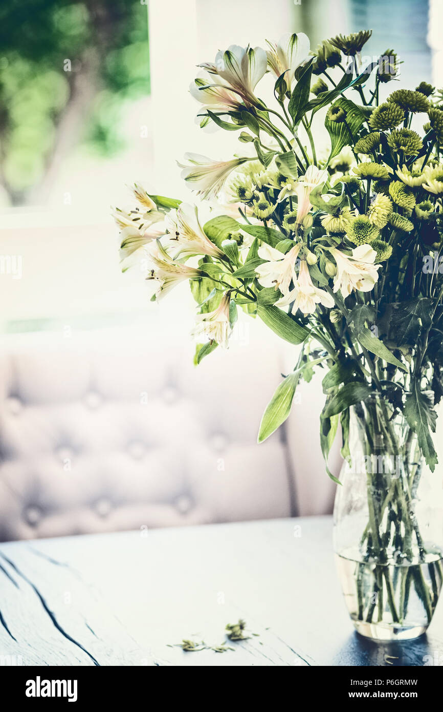 Summer flowers bunch in glass vase on table in living room with falling petals. Cozy home and house decoration - Stock Image
