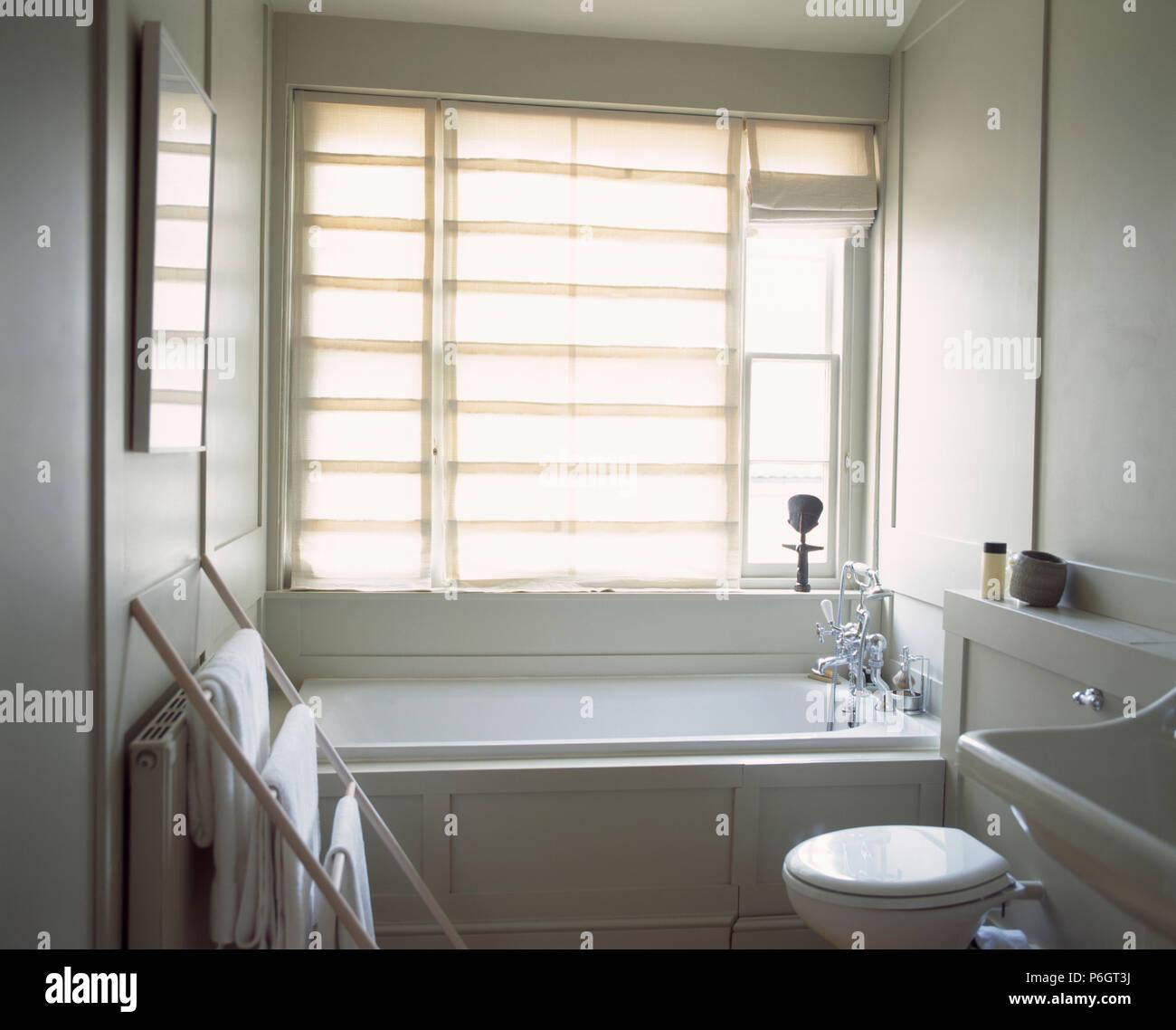White Linen Roman Blind On Window Above Bath In Small White Bathroom - Roman blind bathroom