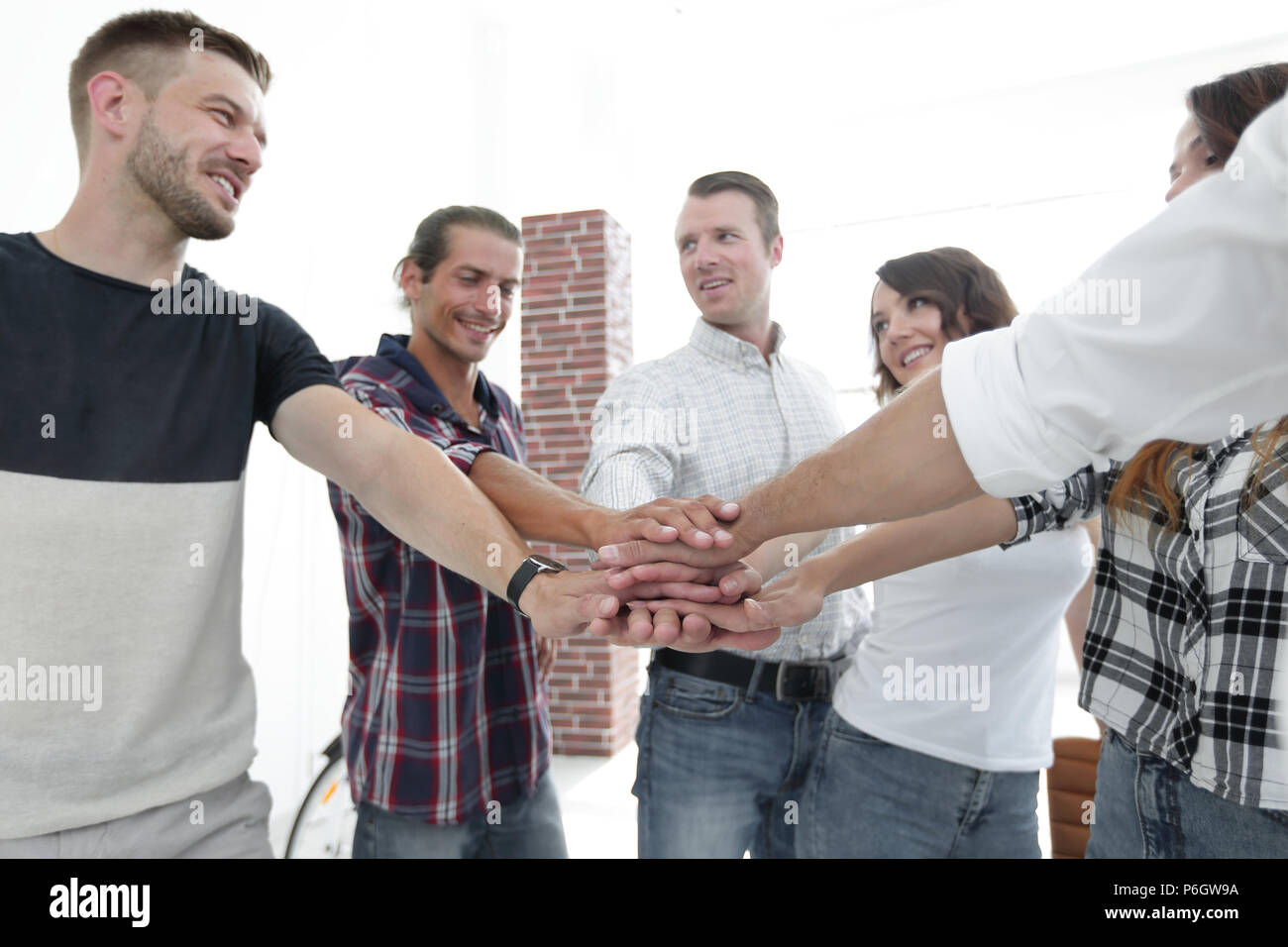 successful team of designers clasped their palms together. - Stock Image