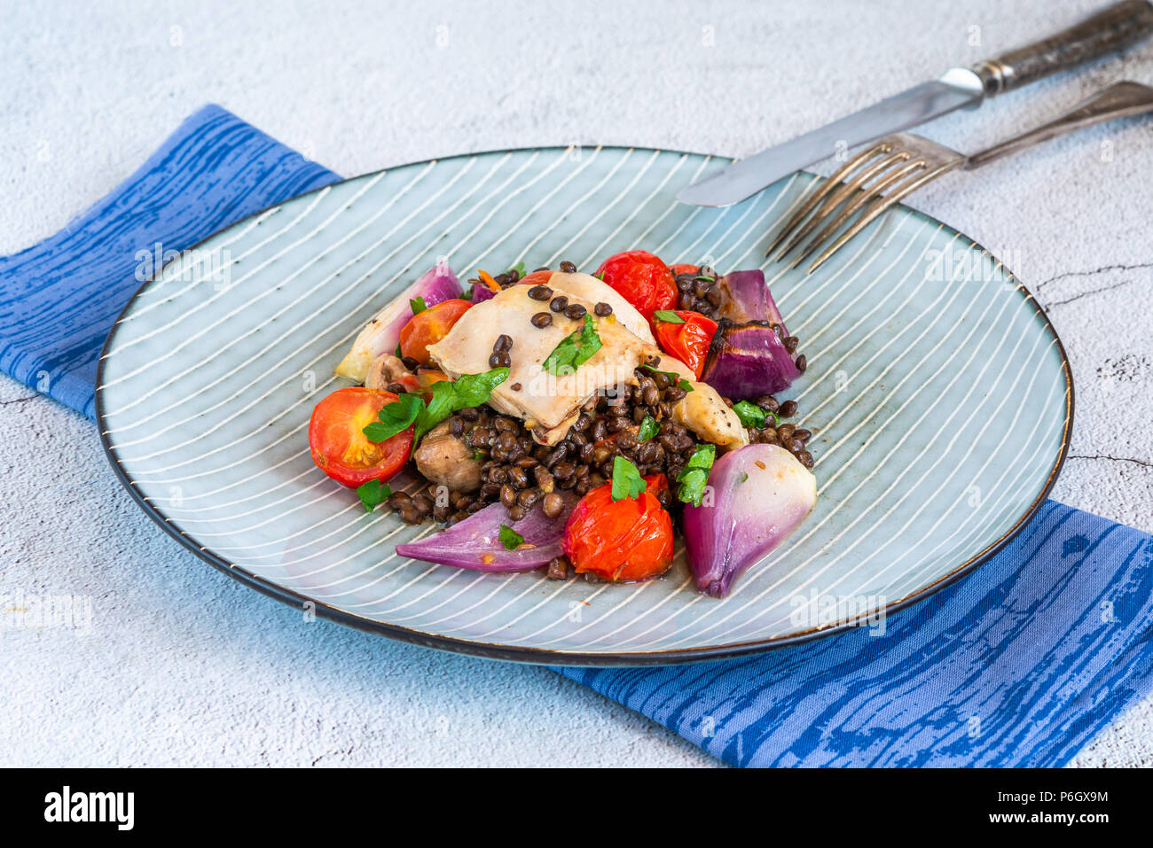 Chicken and cherry tomatoes bake with puy lentils - Stock Image