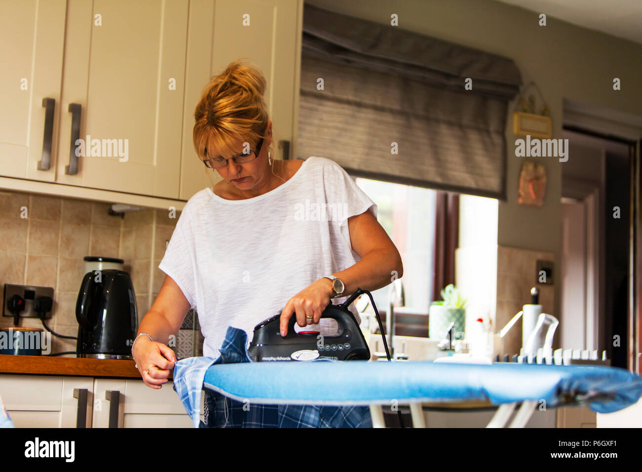 Woman ironing clothes, domestic chores, ironing clothes, woman using iron, ironing, pressing clothes, using ironing board, woman using iron, housework - Stock Image