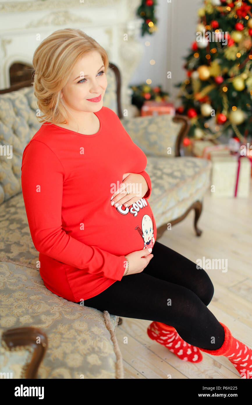 Pregnancy Christmas Sweater.Blonde Pregnant Woman Wearing Red Sweater Hugging Bely And
