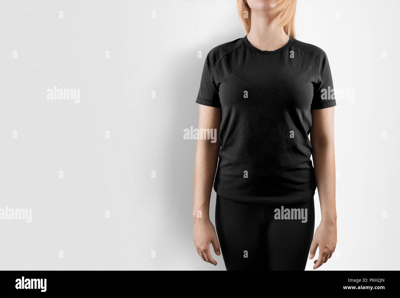 Blank black t-shirt design mockup. Women stand near wal in gray tshirt clear template front mock up. Empty female apparel uniform singlet model. Sweat tee shirt plain dress surface ready for print. - Stock Image
