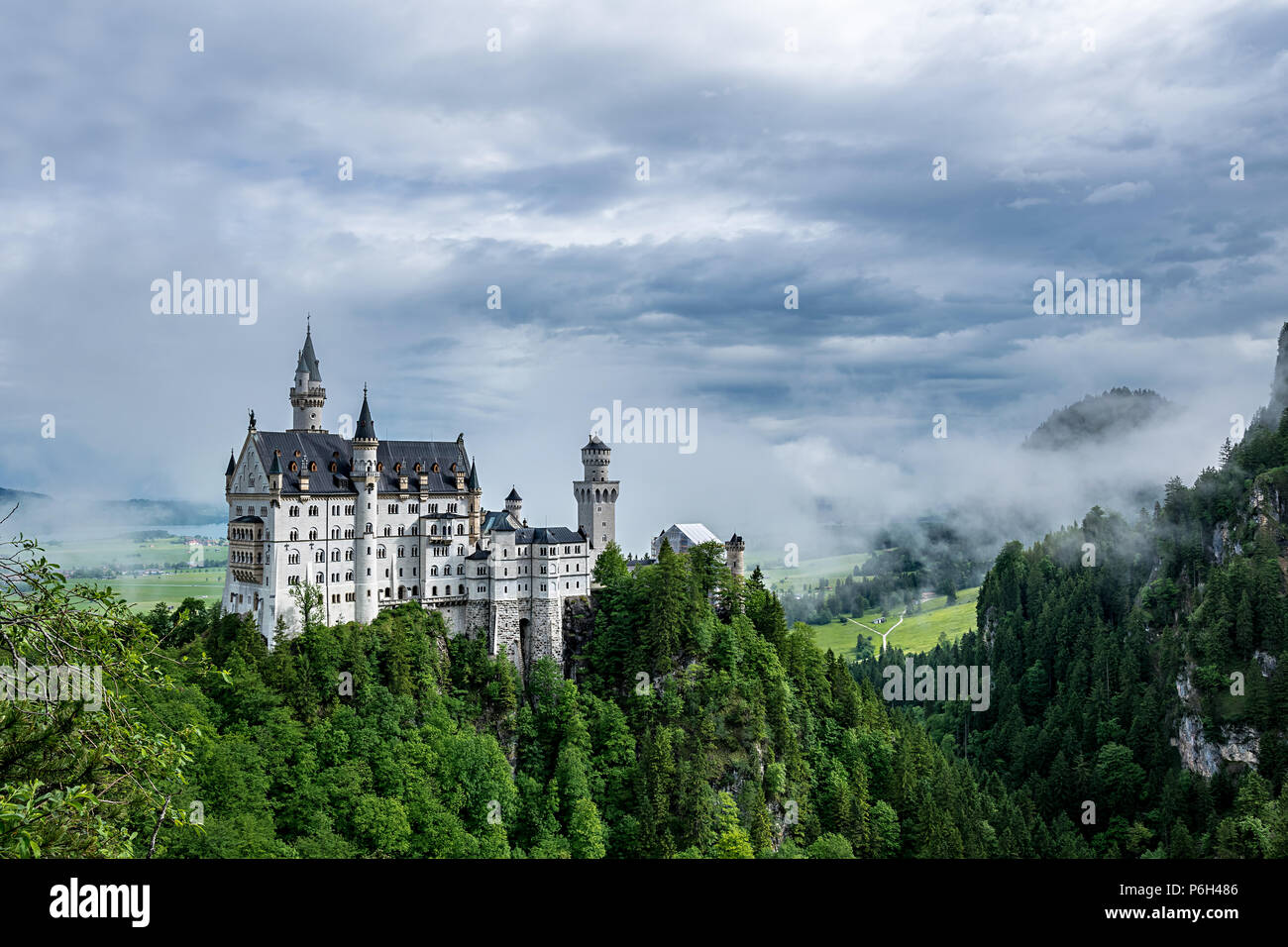 Castel called Neuschwanstein in bavaria with clouds on the sky and a little fog on a sunny day - Stock Image
