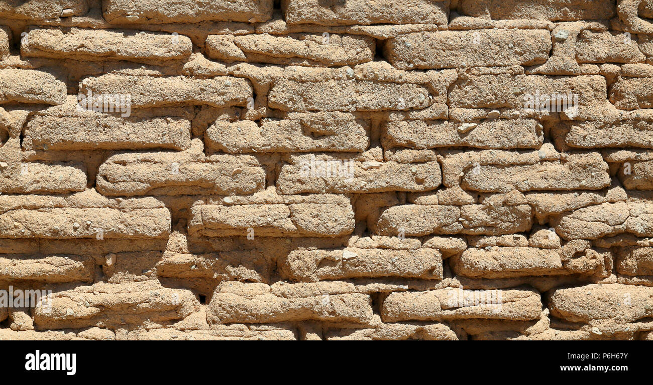 Handmade mud-brick wall creating a pattern and texture with sunlight forming shadows - Stock Image