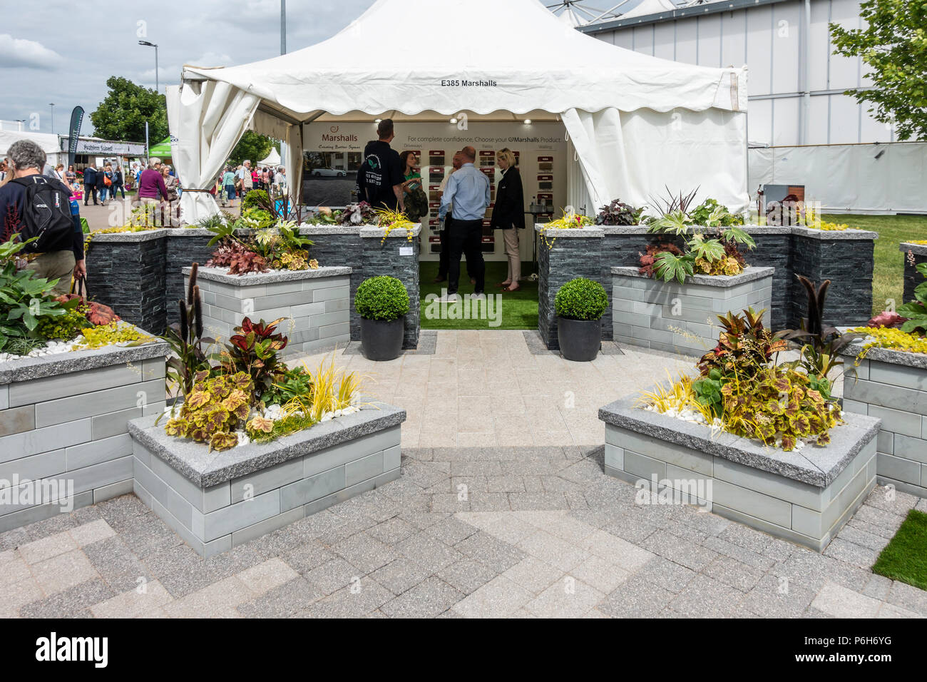 A modern, contemporary show garden featuring hard landscaping products - slabbing, walling, raised beds, by Marshalls: Gardeners' World Live, NEC, - Stock Image