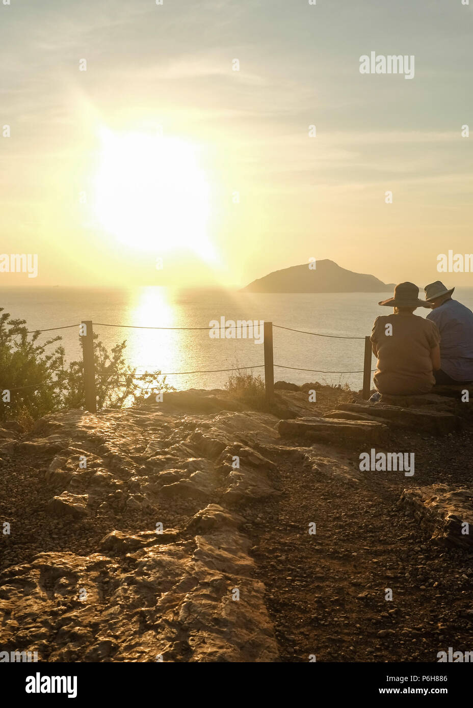 Hatted Couple enjoying the ocean views from Cape Sounion (Temple of Poseidon ) as the Sun begins to set. East Attica, Greece. Stock Photo