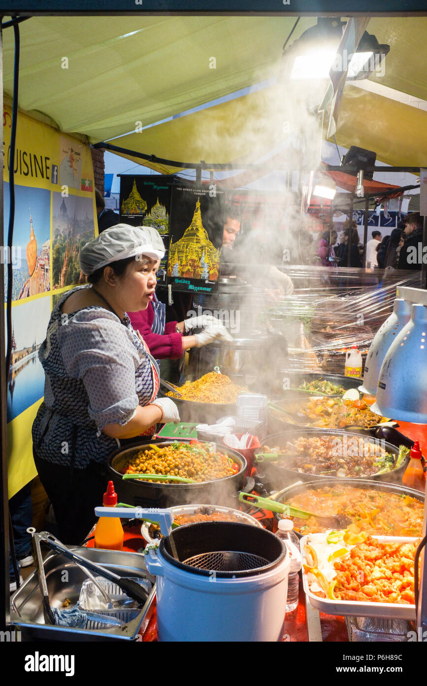 Asian food selling various traditional steaming hot and freshly cooked spicy dishes in Street market, Hackney, London, England. Stock Photo
