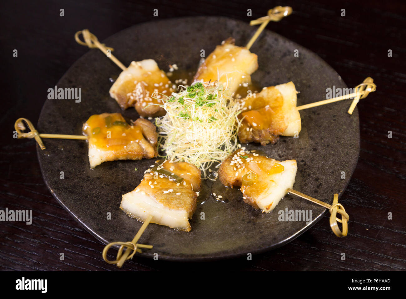 Grilled pork belly served on skewers. The dish features Asian spices.. - Stock Image