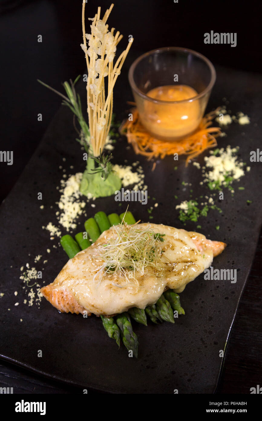 Grilled salmon served with asparagus. It is garnished and served with a glass of Sriracha mayo. - Stock Image