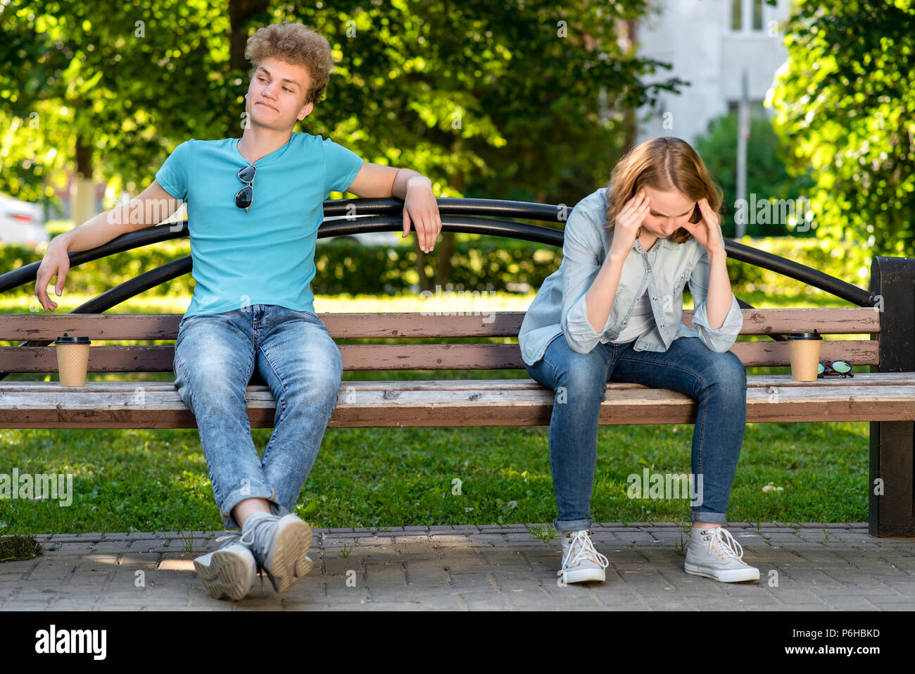 The guy with girl in summer on the bench. Conflicts in a relationship. The girl has a strong headache. Quarrels and misunderstandings in the relations - Stock Image