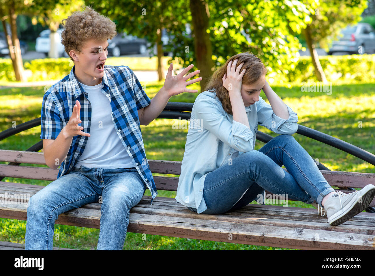 The guy with the girl on the bench. The concept of aggression in a relationship. Scandal in the family. The guy yells at the girl. The girl covered he - Stock Image