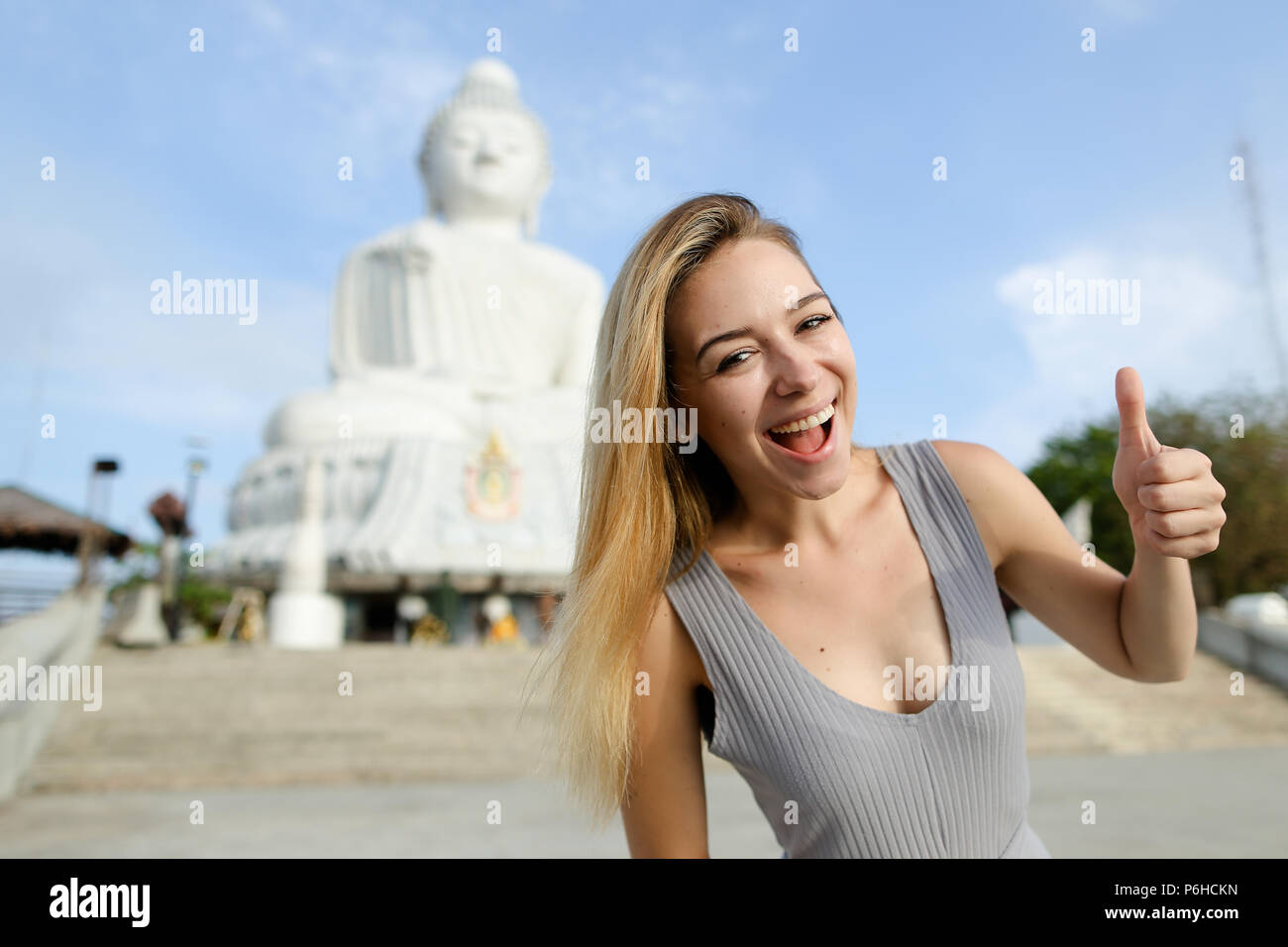 Young smiling girl showing thumbs up, white Buddha statue in Phuket in background. - Stock Image