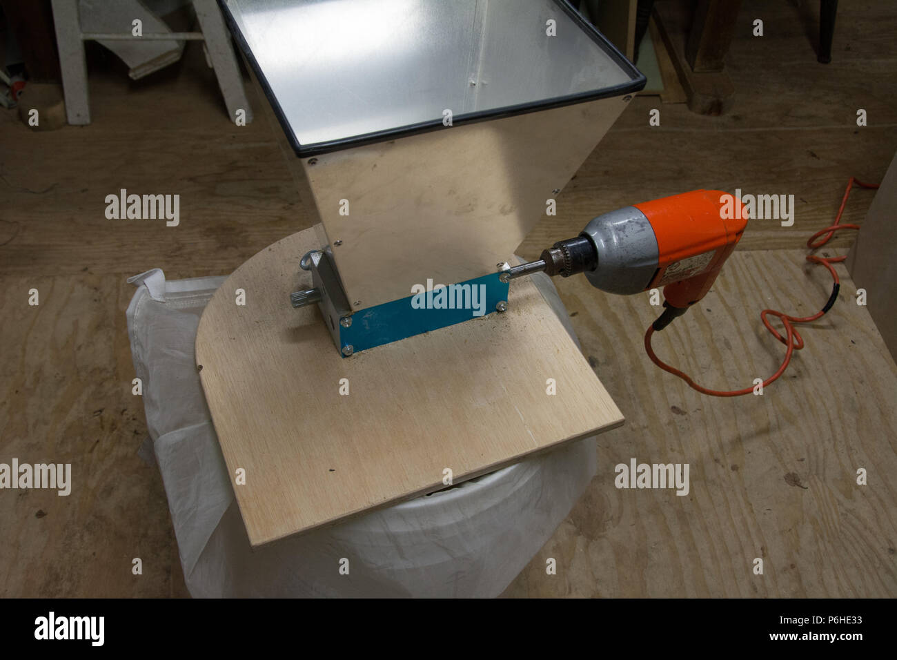 An amateur grain mill setup with a power drill to turn the grinding rollers - Stock Image