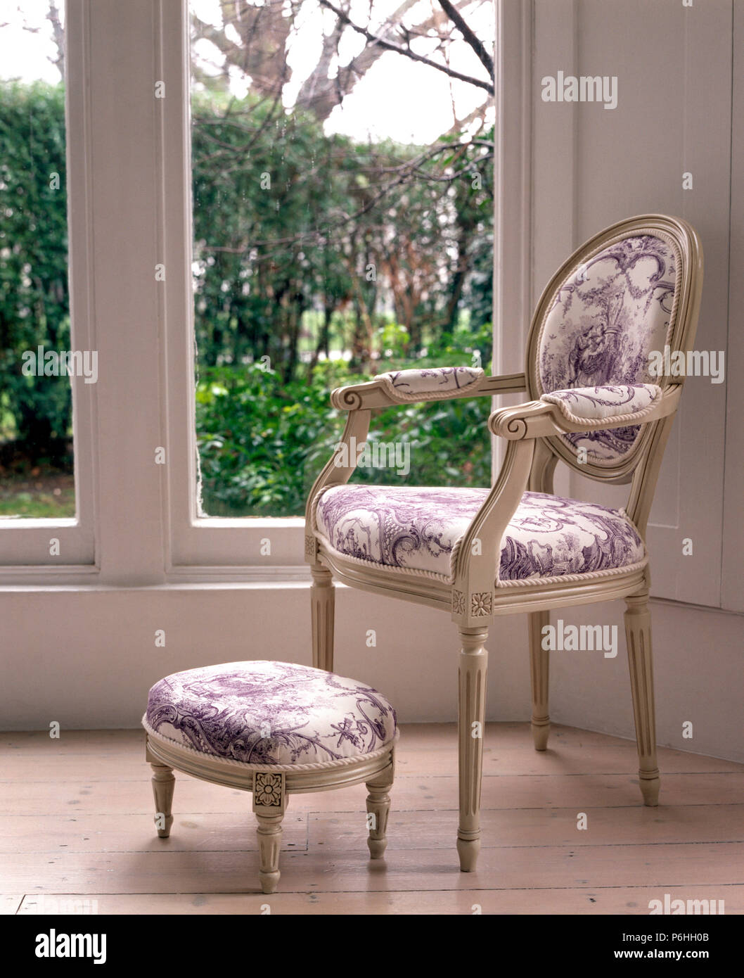 French style chair and footstool upholstered in mauve Toile de Jouy fabric in front of a large window - Stock Image
