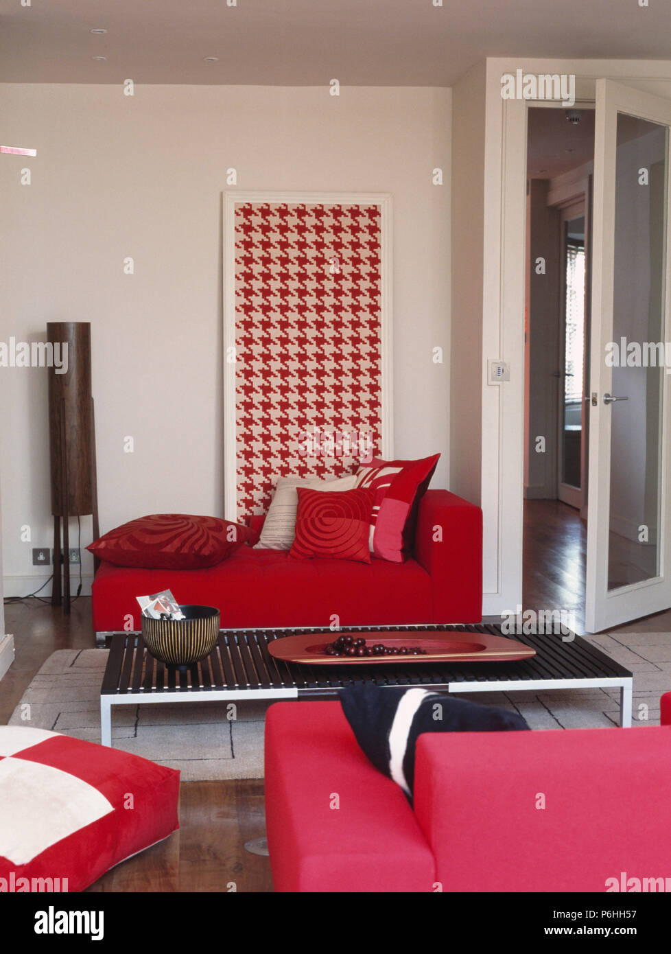 Patterned red cushions on bright red sofa in front of large red+ ...