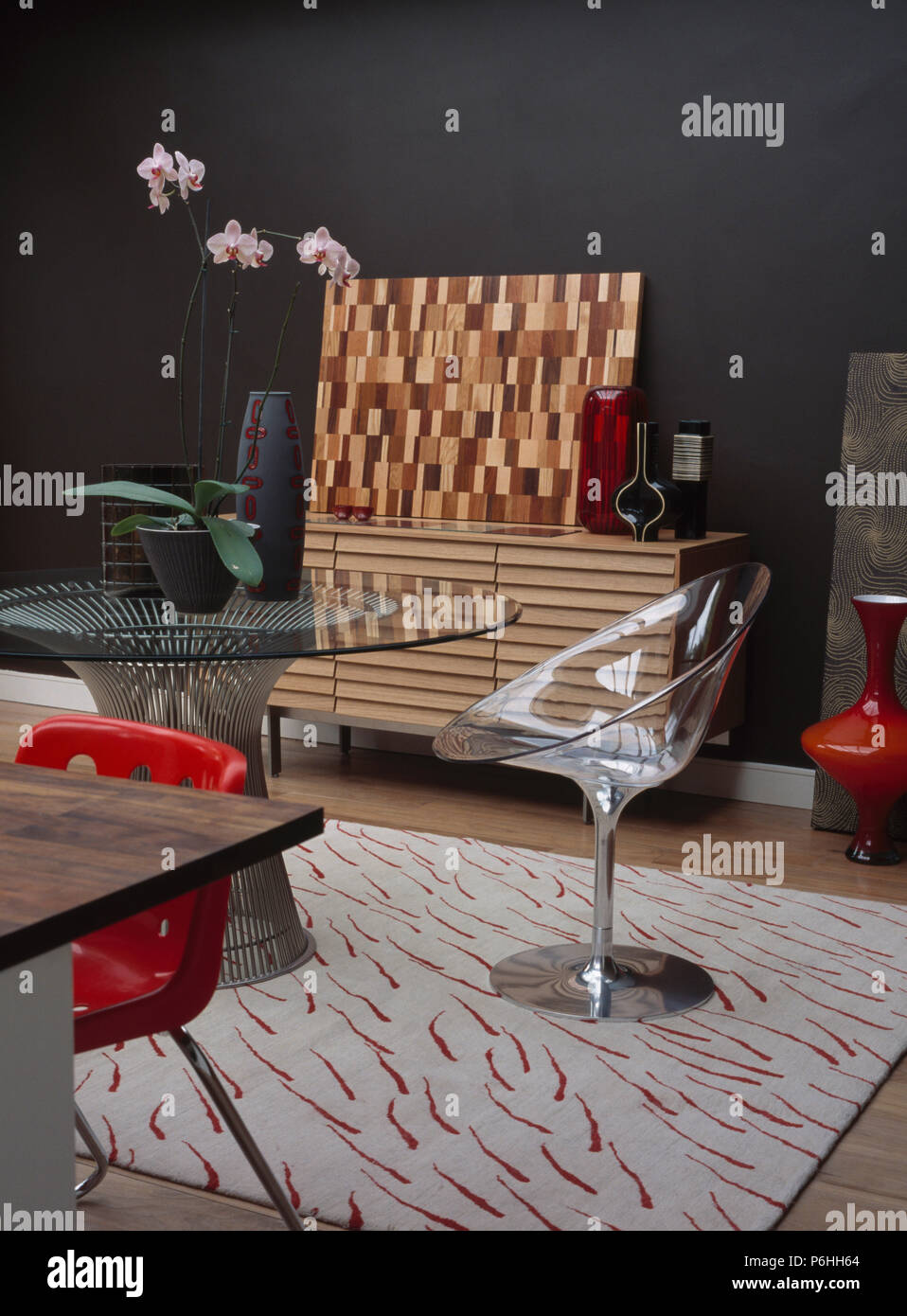 Acrylic pedestal chair and glass-topped circular metal table in modern living room with patterned white rug Stock Photo