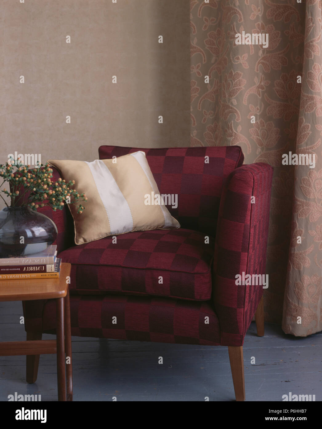 Striped cushion on maroon upholstered chair in front of beige textured floral curtains - Stock Image