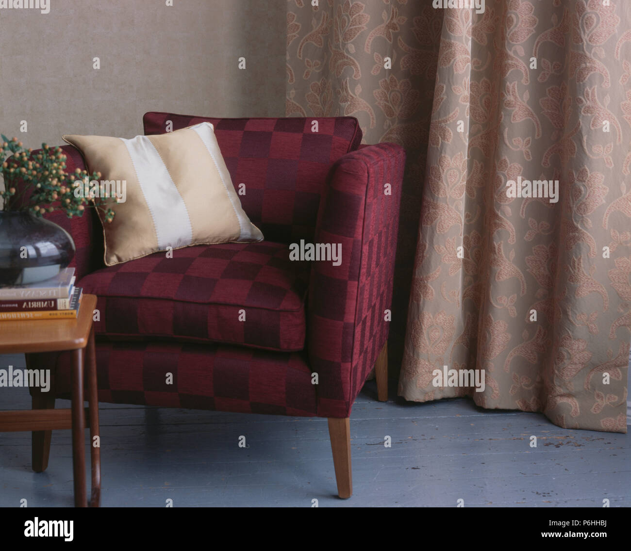 Striped beige cushion on upholstered maroon chair in front of textured floral curtains - Stock Image