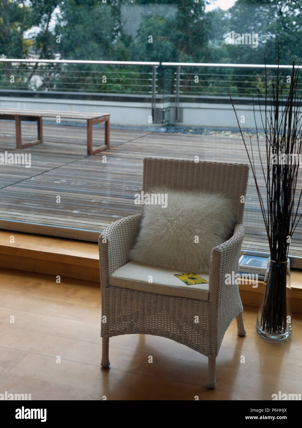 Modern Living Room With Faux Fur Cushion On White Wicker Chair In Front Of  Large Window With View Of Decked Terrace