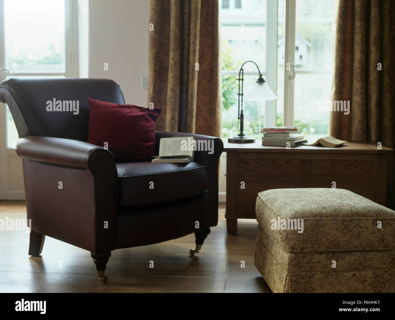 Brown leather armchair and beige ottoman stool beside desk in