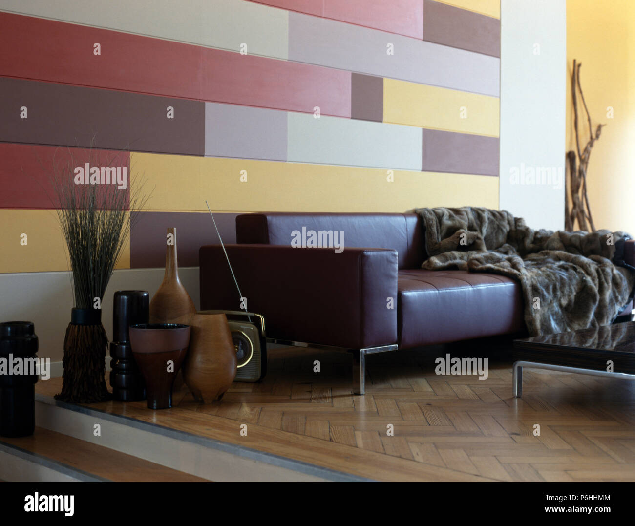 Collection of tall wooden pots beside brown leather sofa with faux fur throw in split-level living room with painted wall - Stock Image