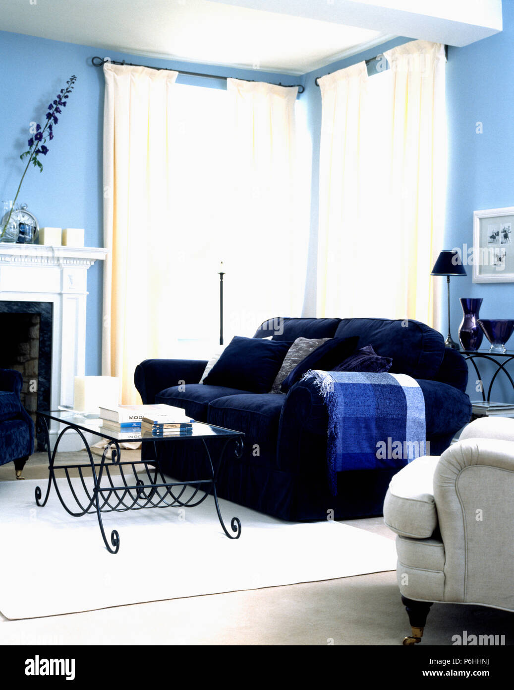Glass-topped wrought-iron coffee-table and dark blue sofa ...