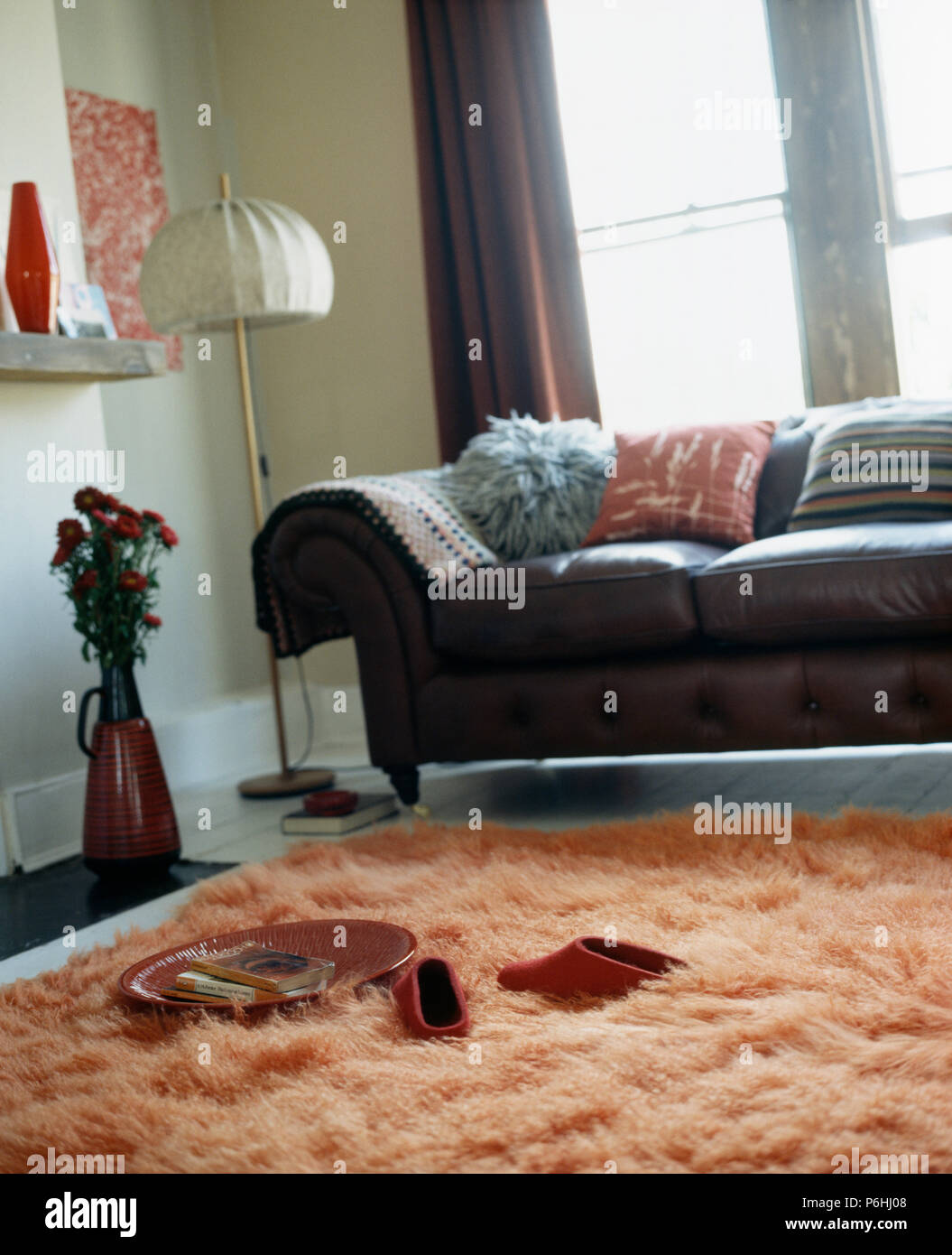 Black Leather Sofa And Orange Faux Fur Rug In Modern Living Room