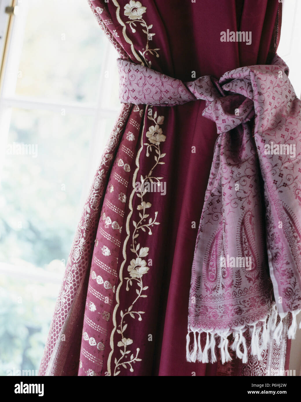 Close-up of red silk curtain with embroidered edging and mauve silk tie-back - Stock Image
