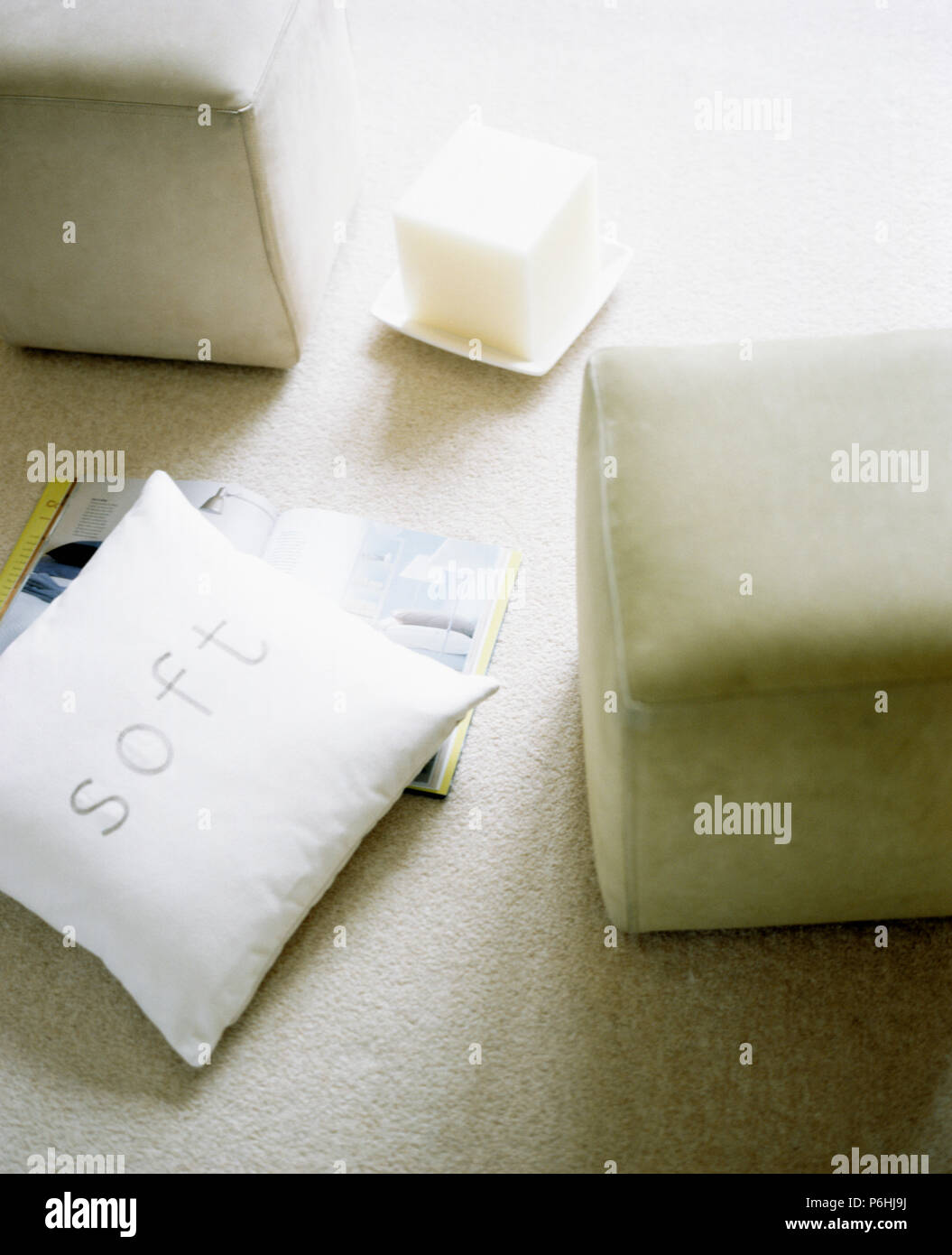 Close-up of white cushion and upholstered cube stool - Stock Image