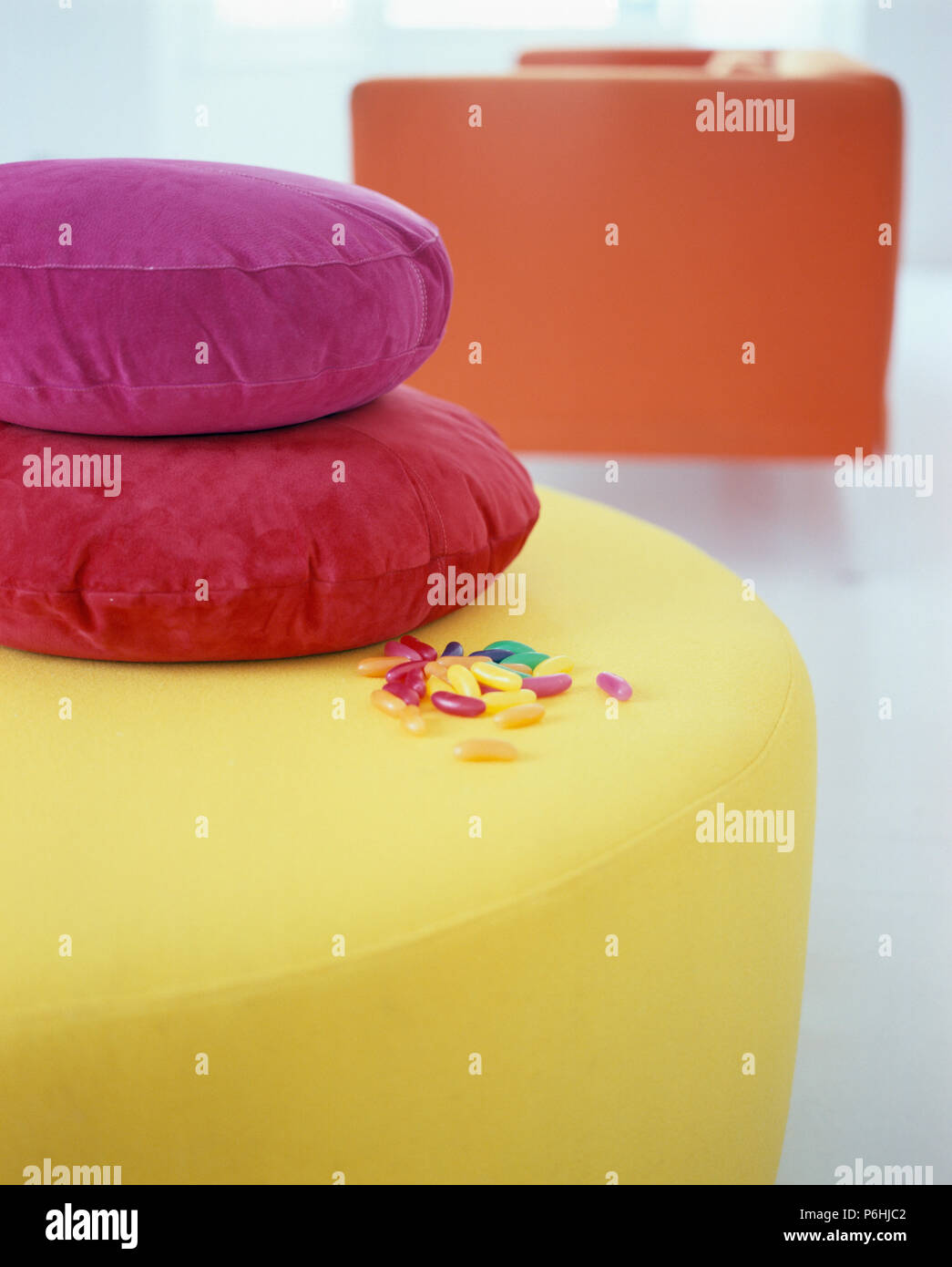Close-up of red and pink cushions on modern circular yellow upholstered stool - Stock Image