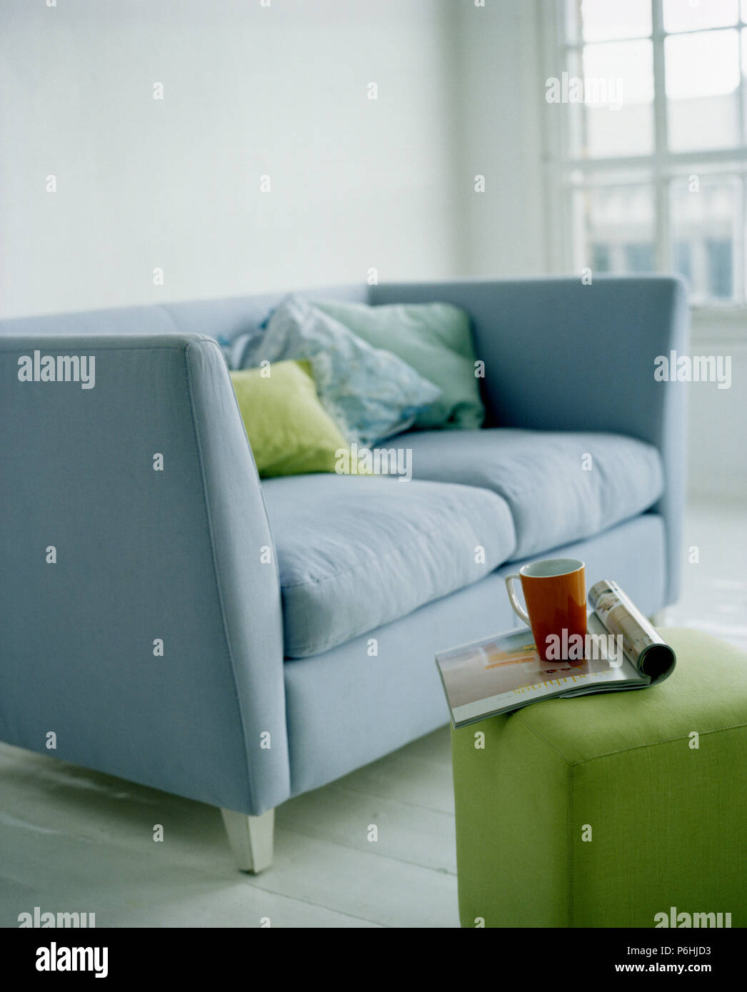 Close Up Of Pale Blue Sofa And Green Cube Stool In Modern Living Room