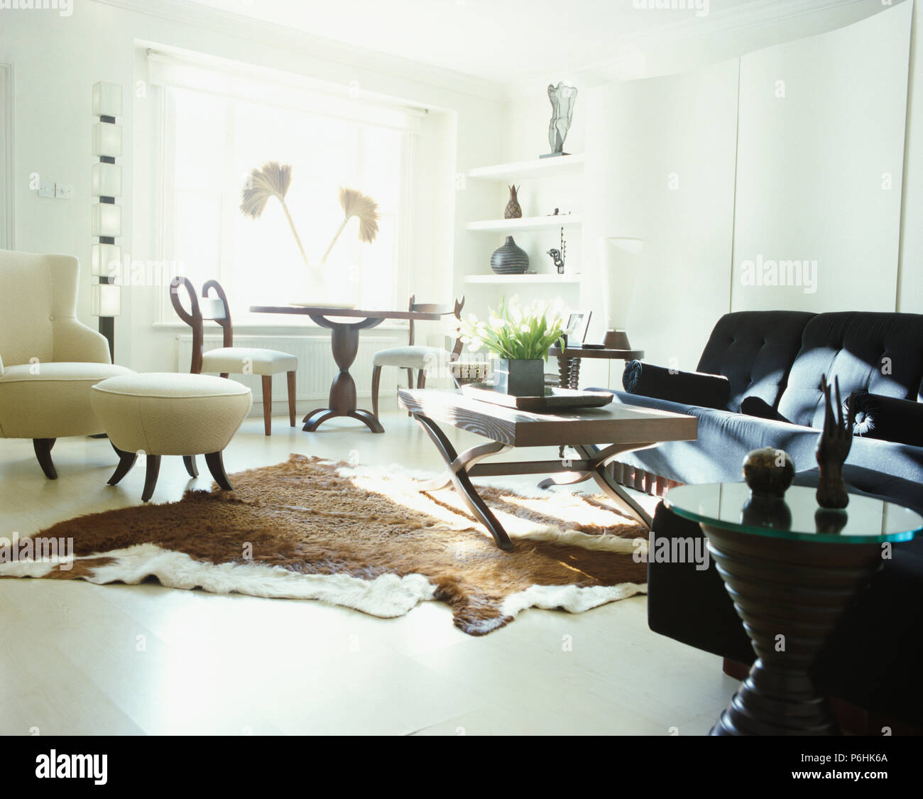 Cow-hide rug on white floor of modern living and dining room Stock ...