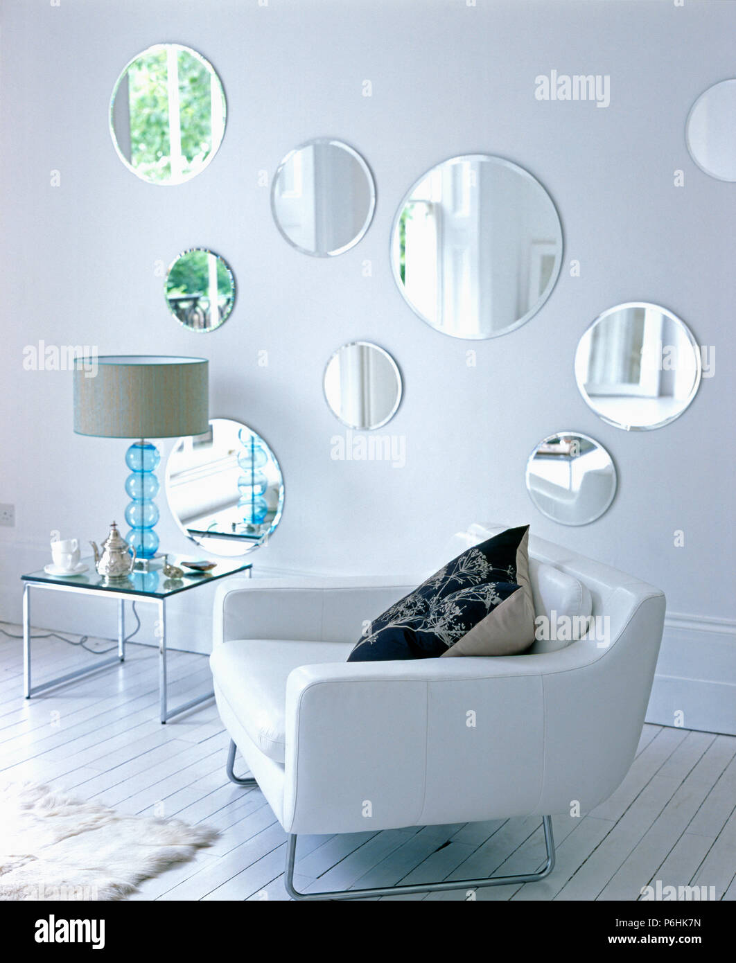 Collection of circular mirrors on wall in modern living room ...