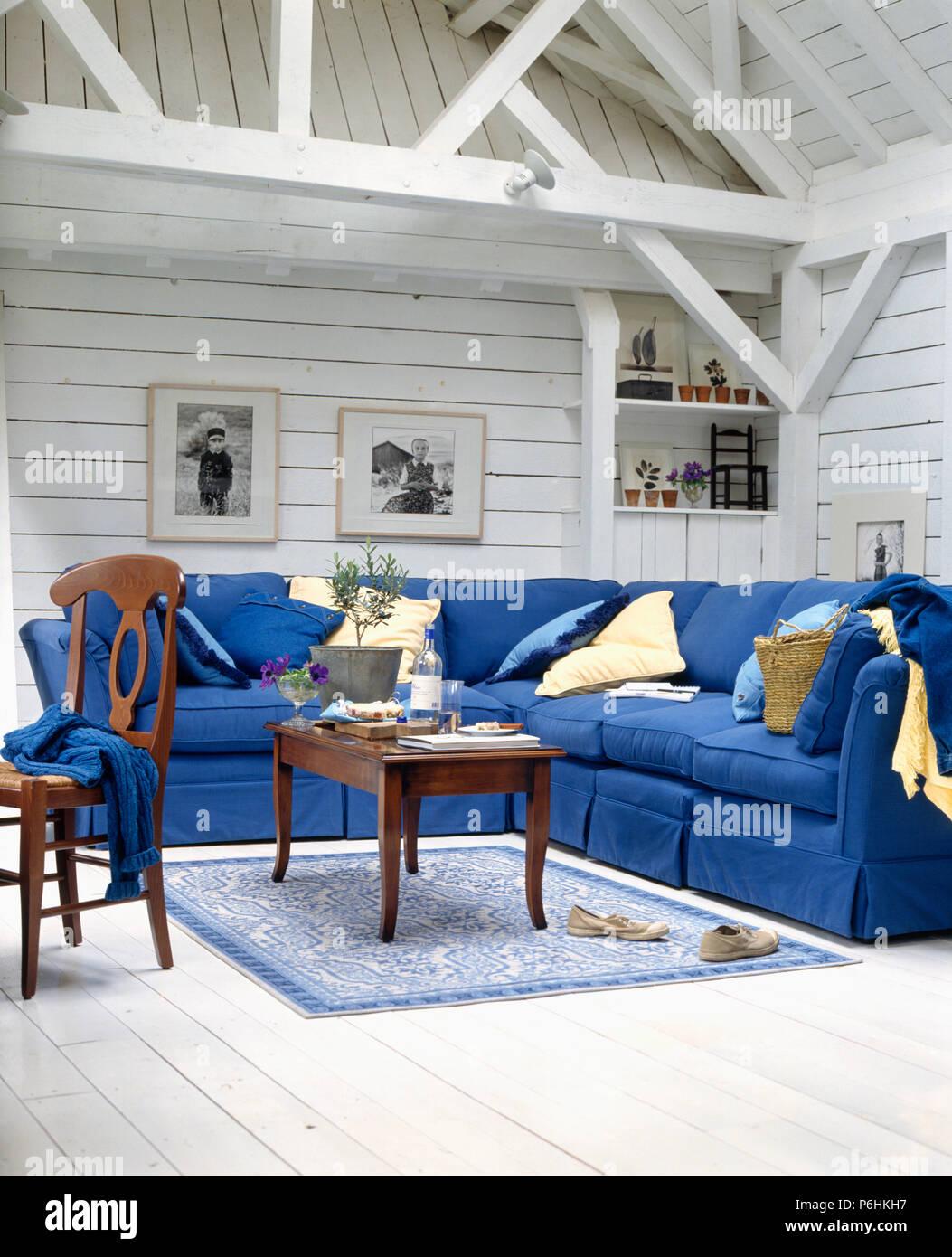 Large bright blue corner sofa in white panelled barn ...