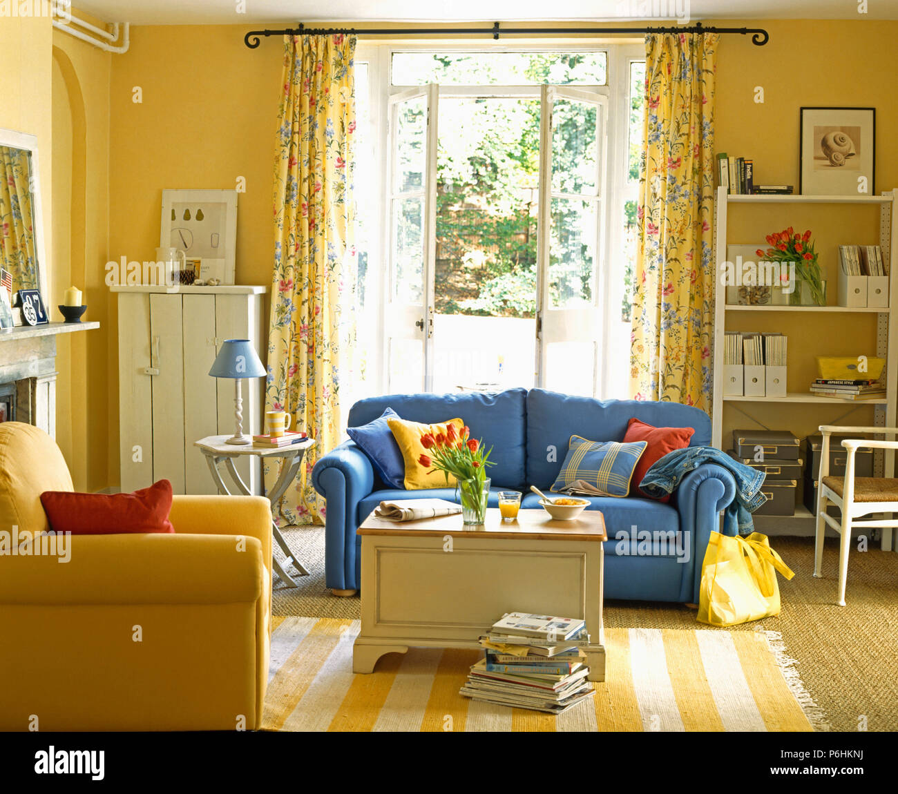 Blue Sofa And Yellow Striped Rug In Yellow Living Room With Painted Chest And French Windows With Floral Curtains Stock Photo Alamy