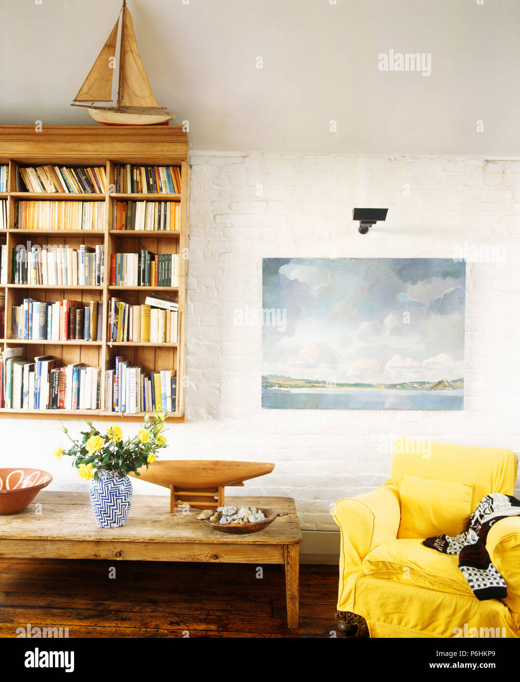 Wall Mounted Bookcase And Seascape Painting In Coastal Living Room With  Yellow Armchair And Rustic Wood Coffee Table